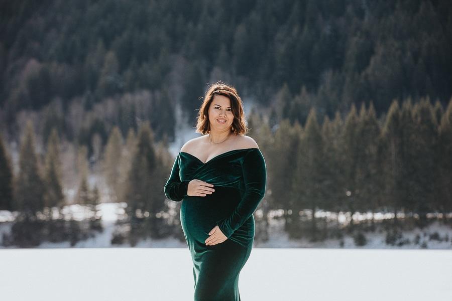 seance photo dans la neige en hiver avec une femme enceinte en robe verte à la montagne près de douvaine